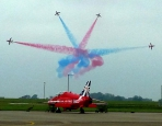 Four aircraft in special display with red and blue trails, red aircraft on ground