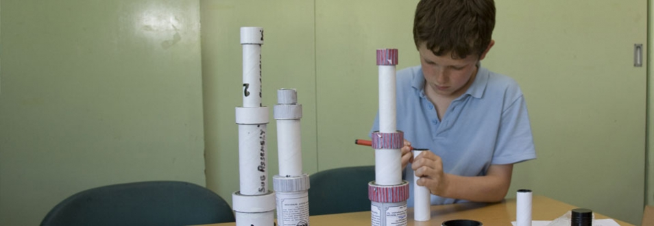 Young boy making a telescope from tubes and lenses