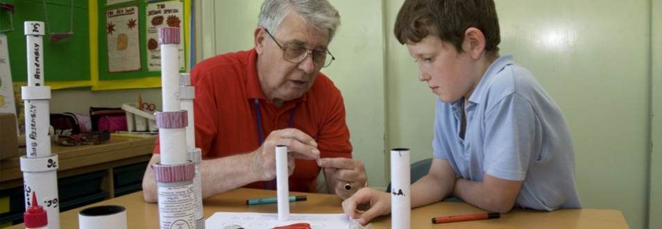 Teacher showing a young boy how the lense fits into the tubes of a telescope