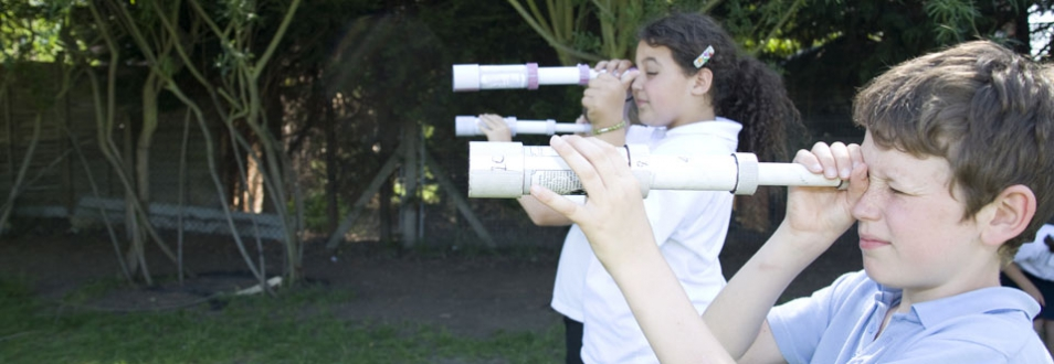 Three children peering through homemade telescopes