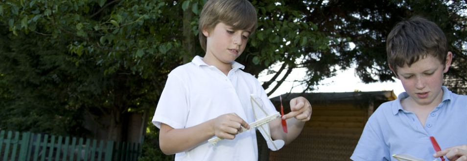 Children winding rubber bands on model helicopters