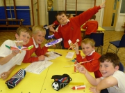 5 lively children around a table about to launch aeroplanes