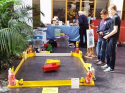 Two boys and small arena with robots on floor