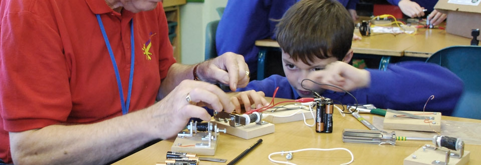 Young boy wiring a morse code buzzer with a teacher