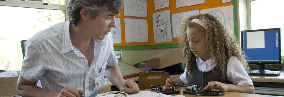 Young girl and teacher working on an electrical device