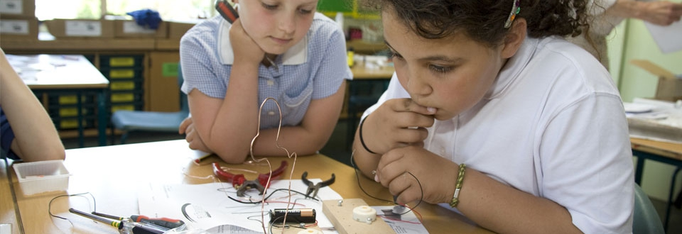 Two young girls working on an electrical game in a classroom