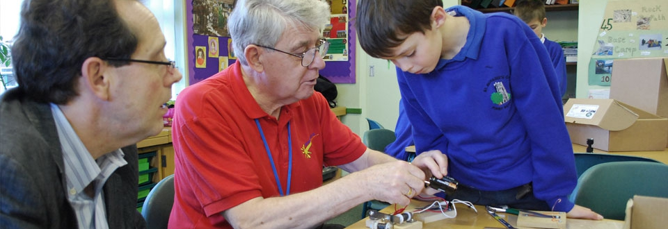 Teacher showing a young boy how to wire up an electrical device
