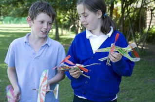 Young girl and boy holding rubber band powered model helicopters