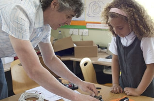 Teacher showing a young girl how to make a model in a classroom