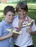 Two young boys holding rubber band powered model helicopters