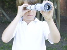 Young boy gazing through his telescope