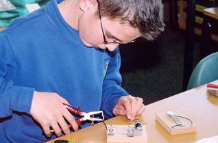 Young boy wiring an electrical device in a classroom