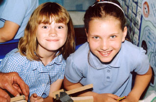 Two young girls smiling in a classroom