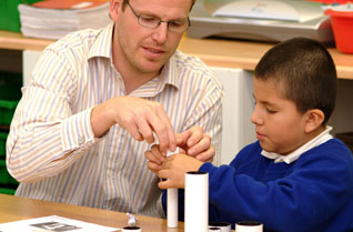 Teacher showing a young boy how to make a telescope