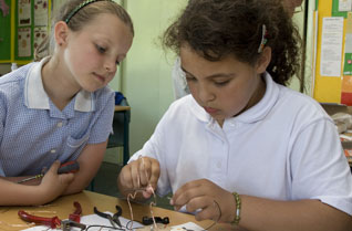 Two young girls building a wire buzzer game