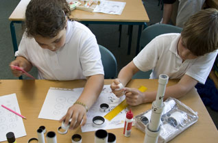 Boy and a girl building a cardboard tube telescope in a classroom