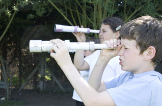 Children looking through cardboard tube telescopes outside