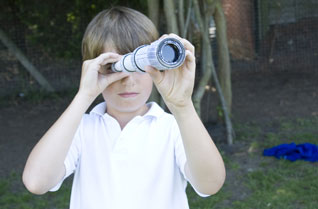 Young boy looking at the camera through a cardboard tube telescope