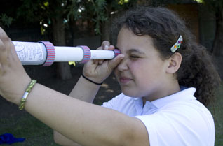 Young girl looking through a cardboard tube telescope