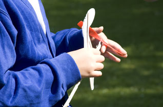 Girl winding the rubber band on a model helicopter