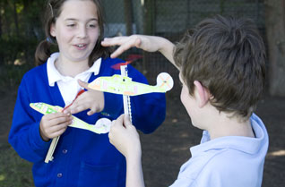 Young girl and boy winding the rubber bands on model helicopters