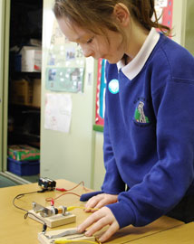 Young girl using a morse key buzzer in a classroom