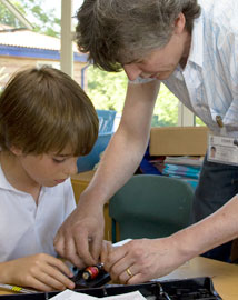 Teacher helping a young boy to wire an electrical device in a classroom