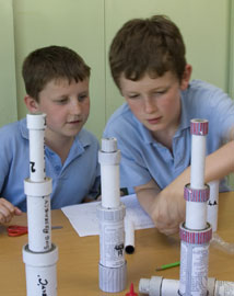 Two young boys making a cardboard tube telescope in a classroom