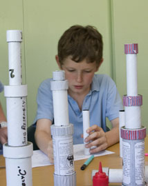 Young boy making a cardboard tube telescope in a classroom