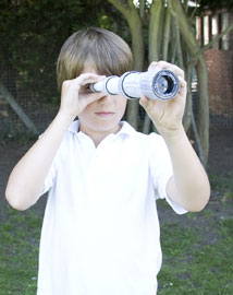 Young boy looking through a cardboard tube telescope outside