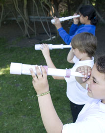 Three children looking through cardboard tube telescopes outside