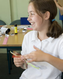 Young girl winding the propeller on a model helicopter in a classroom