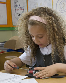 Young girl using a screwdriver on an electrical device in a classroom